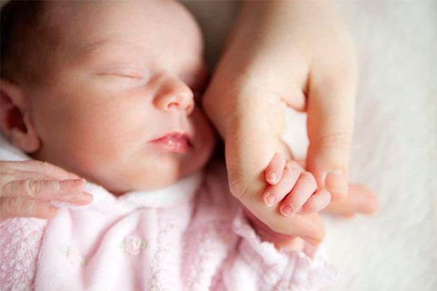 младенец держит маму за руку