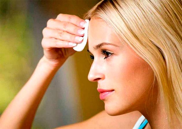 молодая женщина протирает лицо ватным диском