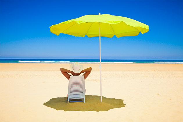 девушка под зонтом на пляже