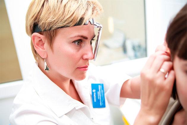 врач осматривает ухо пациента
